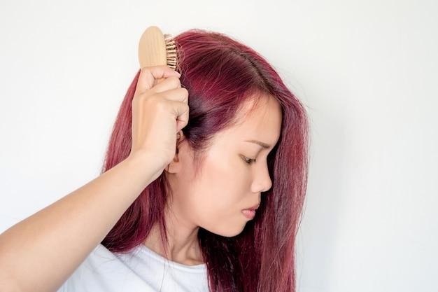 A mulher comping seu cabelo lentamente e ela tem problema de perda de cabelo