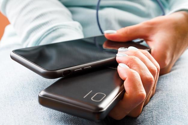 A mulher conectou o carregador com o telefone no escritório ou em casa. banco de poder.