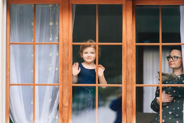 A mulher considerável com gatinho nas mãos olha através da janela grande com sua filha bonita