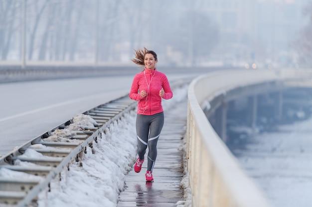 A mulher consideravelmente caucasiano com rabo de cavalo vestiu-se no sportswear que corre na ponte no inverno. conceito de estilo de vida saudável.