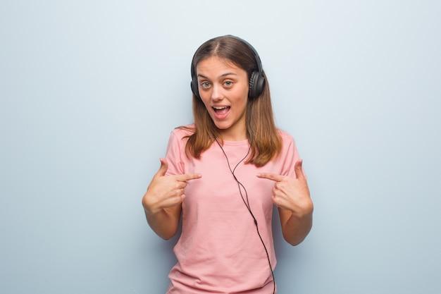A mulher consideravelmente caucasiano dos jovens surpreendida, sente bem sucedida e próspera. ela está ouvindo música com fones de ouvido.