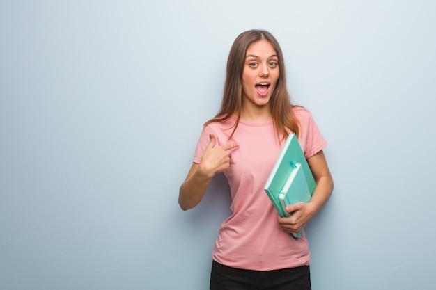 A mulher consideravelmente caucasiano dos jovens surpreendida, sente bem sucedida e próspera. ela está segurando livros.