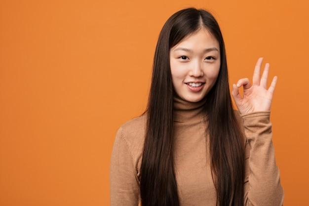 A mulher consideravelmente chinesa nova alegre e segura mostrando o gesto aprovado.