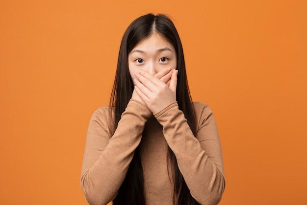 A mulher consideravelmente chinesa nova chocou a boca de coberta com as mãos.