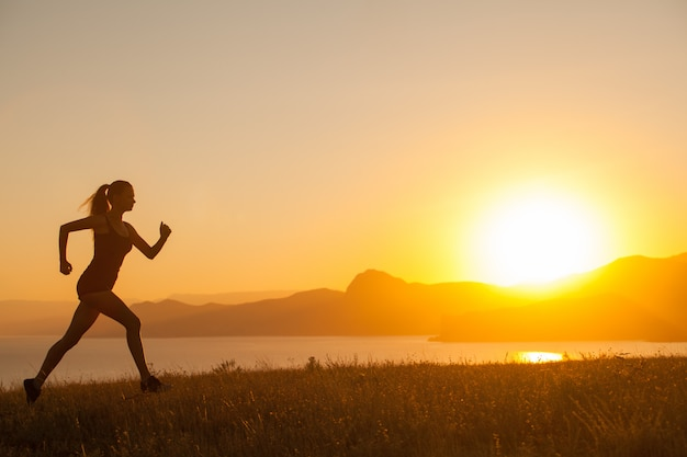 A mulher corre nas montanhas no oceano.