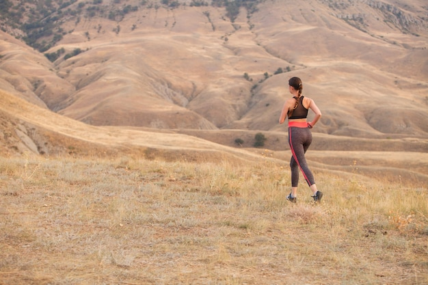A mulher corre nas montanhas