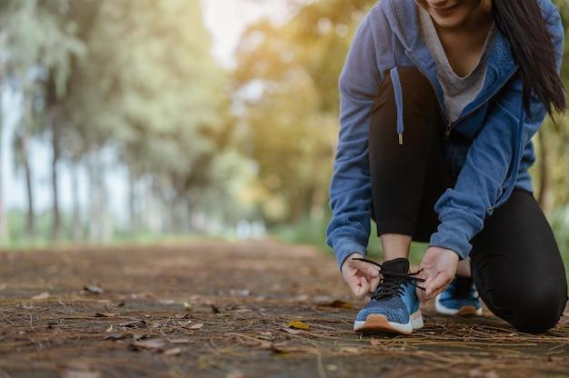 A mulher correndo amarrando cadarços de tênis antes de correr pela rua no parque natural