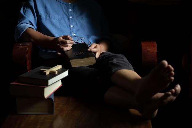 A mulher cristã sentou-se segurando a bíblia