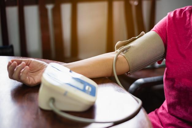 A mulher cuida de sua saúde, verificando sua pressão arterial