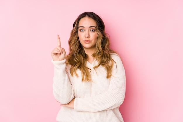 A mulher curvilínea nova que levanta em uma parede cor-de-rosa isolou tendo alguma grande ideia, conceito da faculdade criadora.