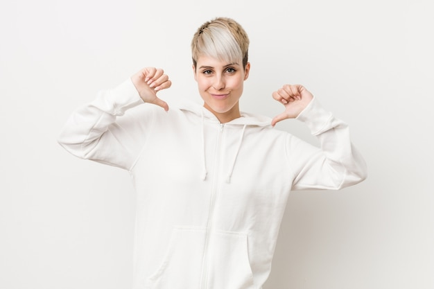 A mulher curvilínea nova que veste um hoodie branco sente orgulhosa e auto-confiante, exemplo a seguir.