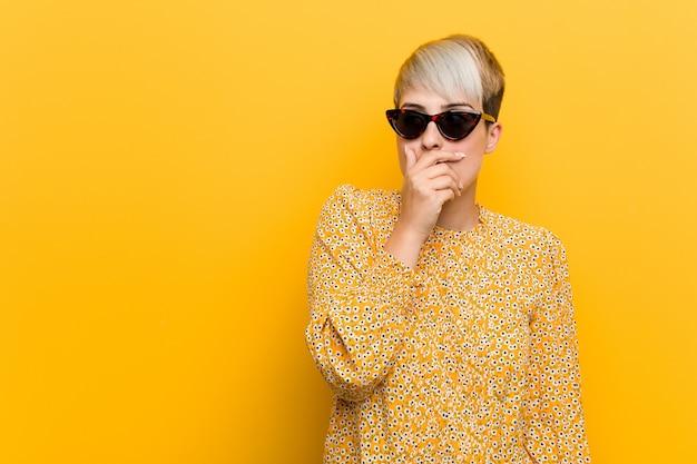 A mulher curvilínea nova que veste um verão floral veste a vista pensativa a um espaço da cópia que cobre a boca com a mão.