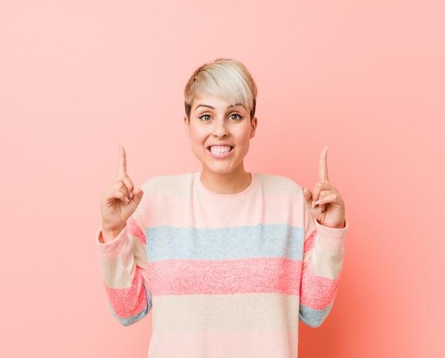 A mulher curvy natural nova indica com ambos os dedos dianteiros acima de mostrar um espaço vazio.