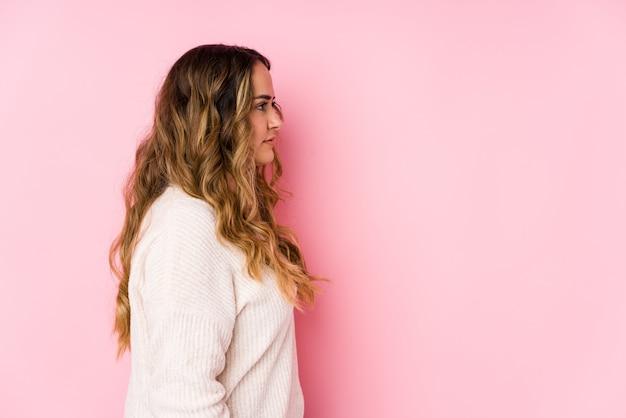 A mulher curvy nova que levanta em uma parede cor-de-rosa isolou olhar esquerdo, pose lateral.