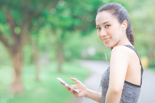 A mulher da aptidão está escutando a música de seu telefone celular ao correr no parque.