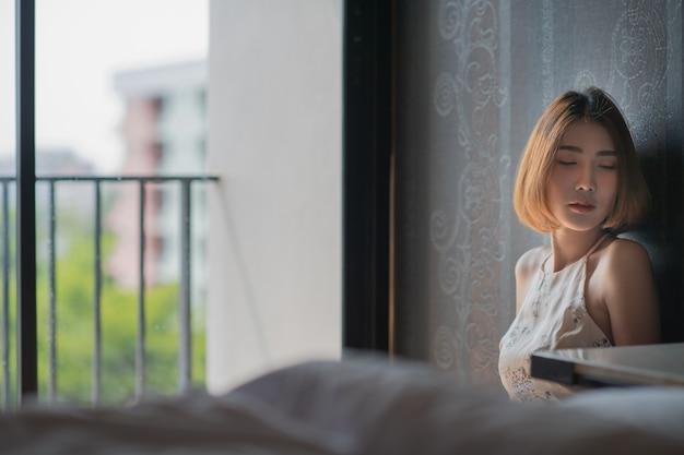 A mulher da depressão senta-se no quarto, mulher asiática triste, livre do espaço da cópia. conceito solitário de modelo asiático.