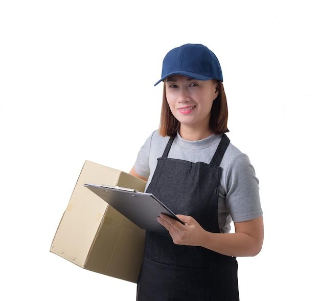 A mulher da entrega na camisa e no avental cinzentos com a pilha de caixas está levando o pacote e está apresentando a recepção do formulário isolado