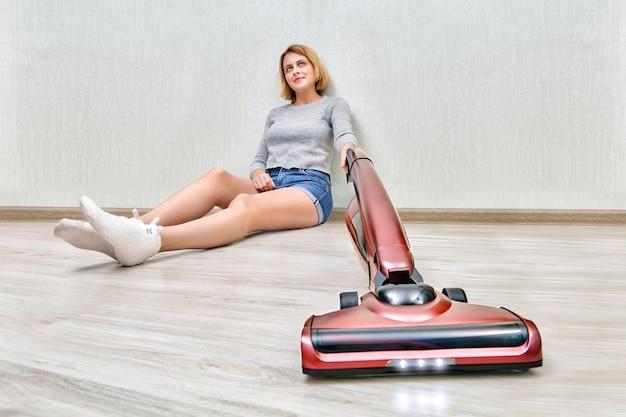 A mulher da limpeza cansada está sentada no chão e limpando a poeira com um aspirador de pó vermelho moderno com luzes led acesas.