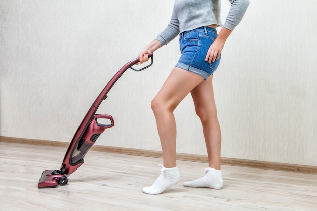 A mulher da limpeza de shorts jeans está passando o aspirador com a ajuda do aspirador de mão sem fio vermelho moderno
