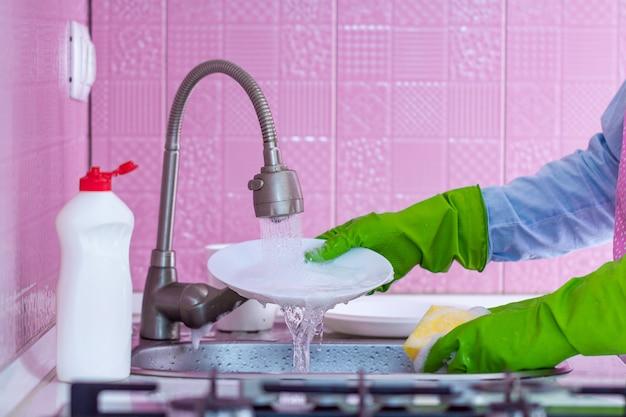 A mulher da limpeza em luvas de borracha verdes e avental lava a louça na cozinha em casa