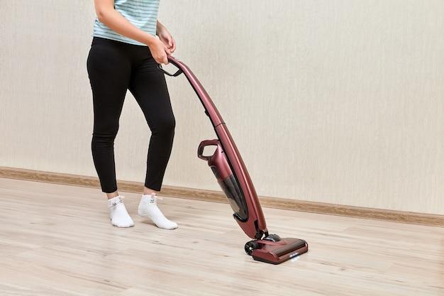 A mulher da limpeza está limpando com a ajuda de um aspirador de pó vertical com luzes led acesas.