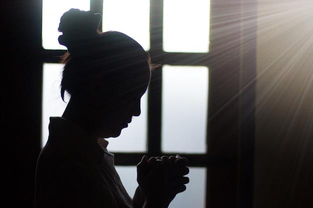A mulher da silhueta reza no por do sol perto da janela.