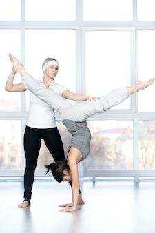 A mulher de ajuda outra mulher para esticar as pernas