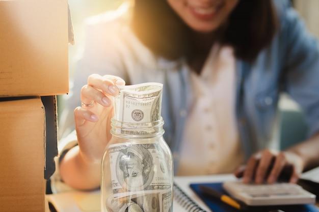 A mulher de ásia que conta o dinheiro das cédulas do dólar de eu sorri com feliz.