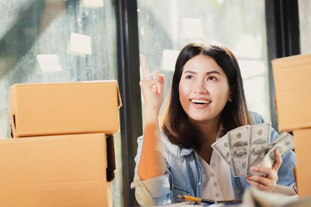 A mulher de ásia que guarda o dinheiro das cédulas do dólar de eu sorri com feliz.