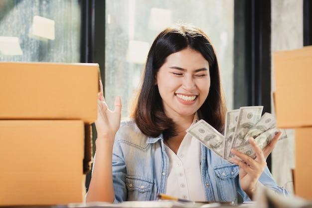 A mulher de ásia que guarda o dinheiro das cédulas do dólar sorri com feliz.