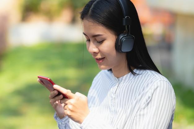 A mulher de ásia que usa o funcionamento do smartphone, escutando a música com relaxa e feliz no feriado.