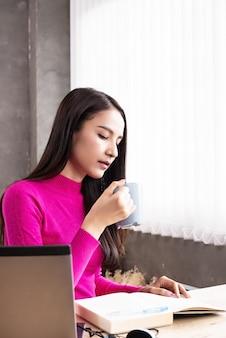 A mulher de beleza, bebendo café e verificar o livro de formulário de dados, trabalhar em casa