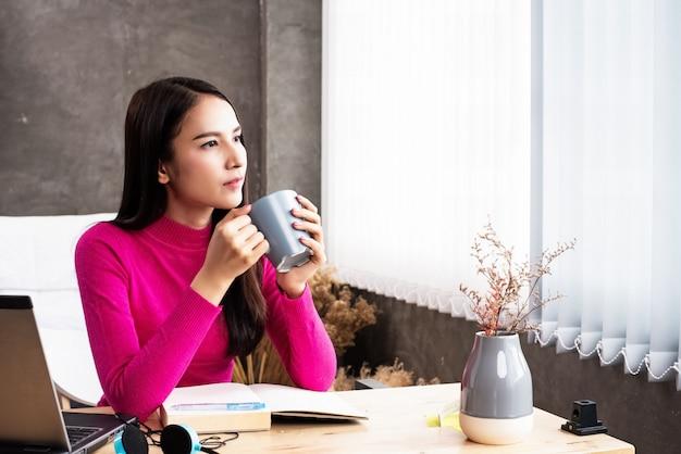 A mulher de beleza segurando a xícara de café de cerâmica na mão, olhando para fora da janela, relaxar o tempo entre o trabalho, luz embaçada em torno de