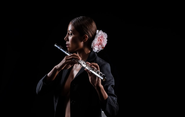 A mulher de beleza segurando flauta nas mãos