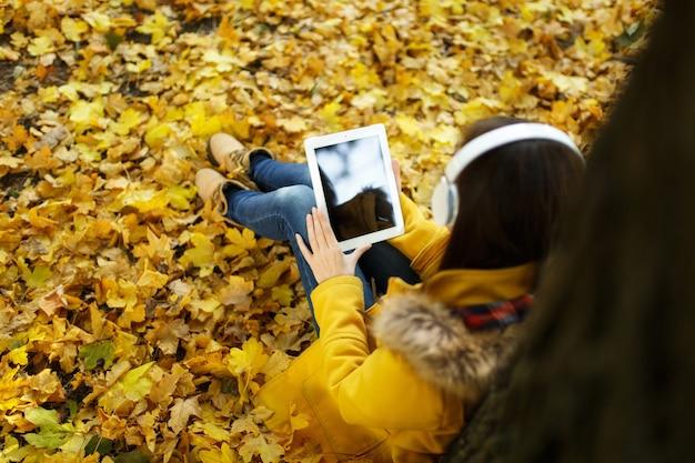 A mulher de cabelos castanhos em um casaco amarelo e calça jeans sentada e ouvindo música debaixo de uma árvore com um tablet nas mãos e fones de ouvido no outono parque da cidade em um dia quente. folhas de outono dourado. vista do topo