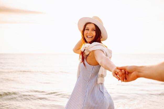 A mulher de cabelos compridos em um chapéu é executada segurando a mão do namorado ao longo da areia vazia da praia do oceano ao pôr do sol