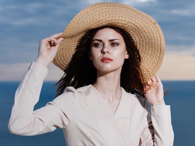 A mulher de chapéu de palha e roupas leves estava no oceano