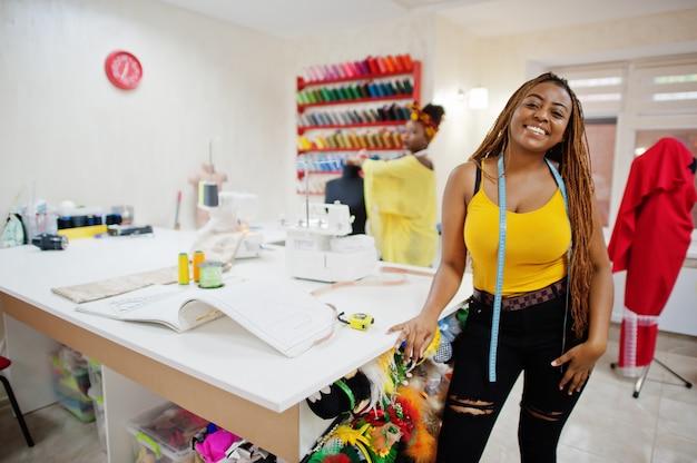 A mulher de duas costureiras africanas costura a roupa na máquina de costura no escritório do alfaiate. garotas costureiras negras.