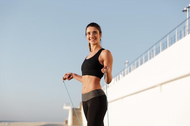 A mulher de esportes feliz jovem sorridente faz exercícios de esporte