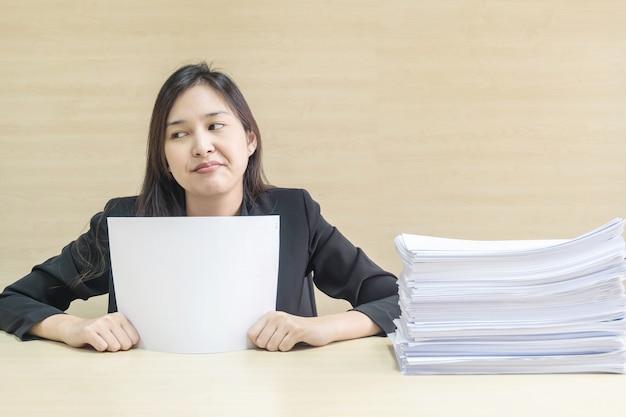 A mulher de funcionamento do close up é chata da pilha do papel de trabalho no conceito do trabalho