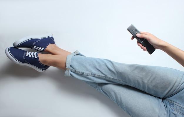 A mulher de jeans e tênis senta e segura o controle remoto da tv. vista do topo.
