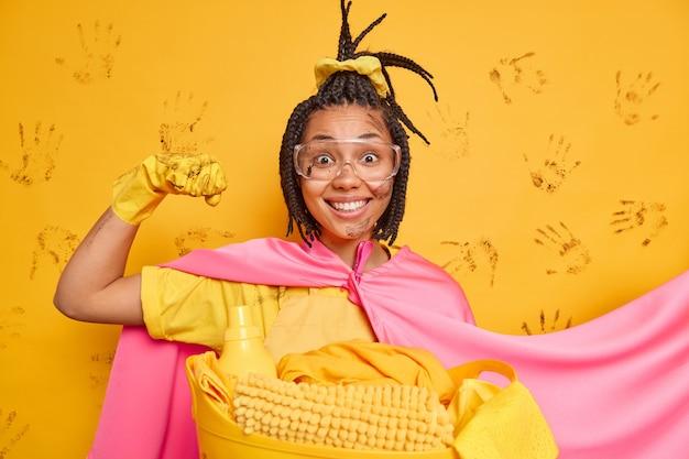 A mulher de limpeza alegre de super-heroína mostra seus músculos e demonstra seu poder, pronta para limpar a sala, usa luvas de borracha e capa isolada sobre a parede amarela
