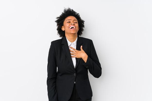 A mulher de negócio afro-americano envelhecida meio contra uma parede branca isolada ri para fora mantendo a mão na caixa.