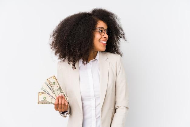 A mulher de negócio afro nova que mantem um carro do crédito isolado a mulher de negócio afro nova que prende um crédito olha de lado a sorrir, alegre e agradável.