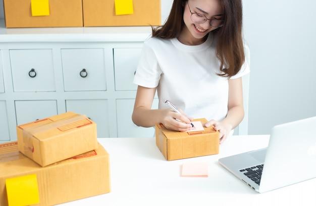 A mulher de negócio asiática do proprietário do adolescente trabalha em casa para a compra e a venda em linha.