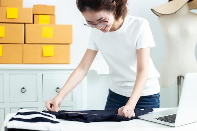 A mulher de negócio asiática do proprietário do adolescente trabalha em casa para compra e venda on-line.