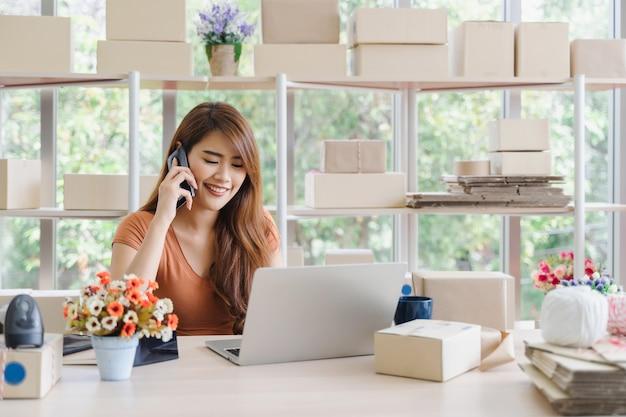 A mulher de negócio asiática feliz bonita nova no vestuário desportivo com smiley está chamando para receber pedidos do cliente com o portátil em seu escritório home da partida, conceito do sme
