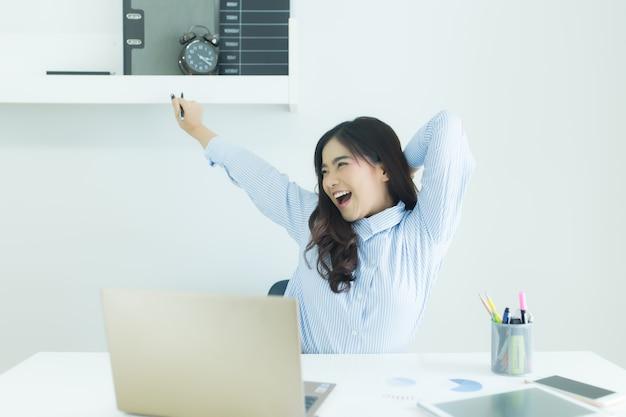 A mulher de negócio asiática nova feliz terminou seu trabalho no local de trabalho.