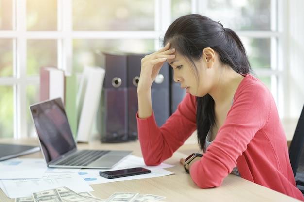 A mulher de negócio asiática séria frustrada do problema ao funcionamento tentou o projeto novo usando o portátil.