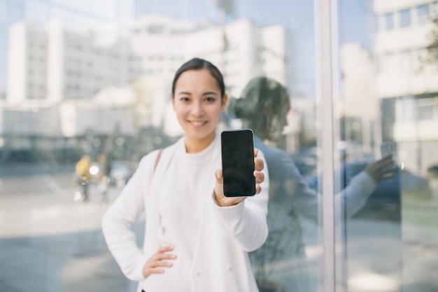 A mulher de negócio bonita asiática adulta está na frente do centro do escritório que mostra sua tela do telefone